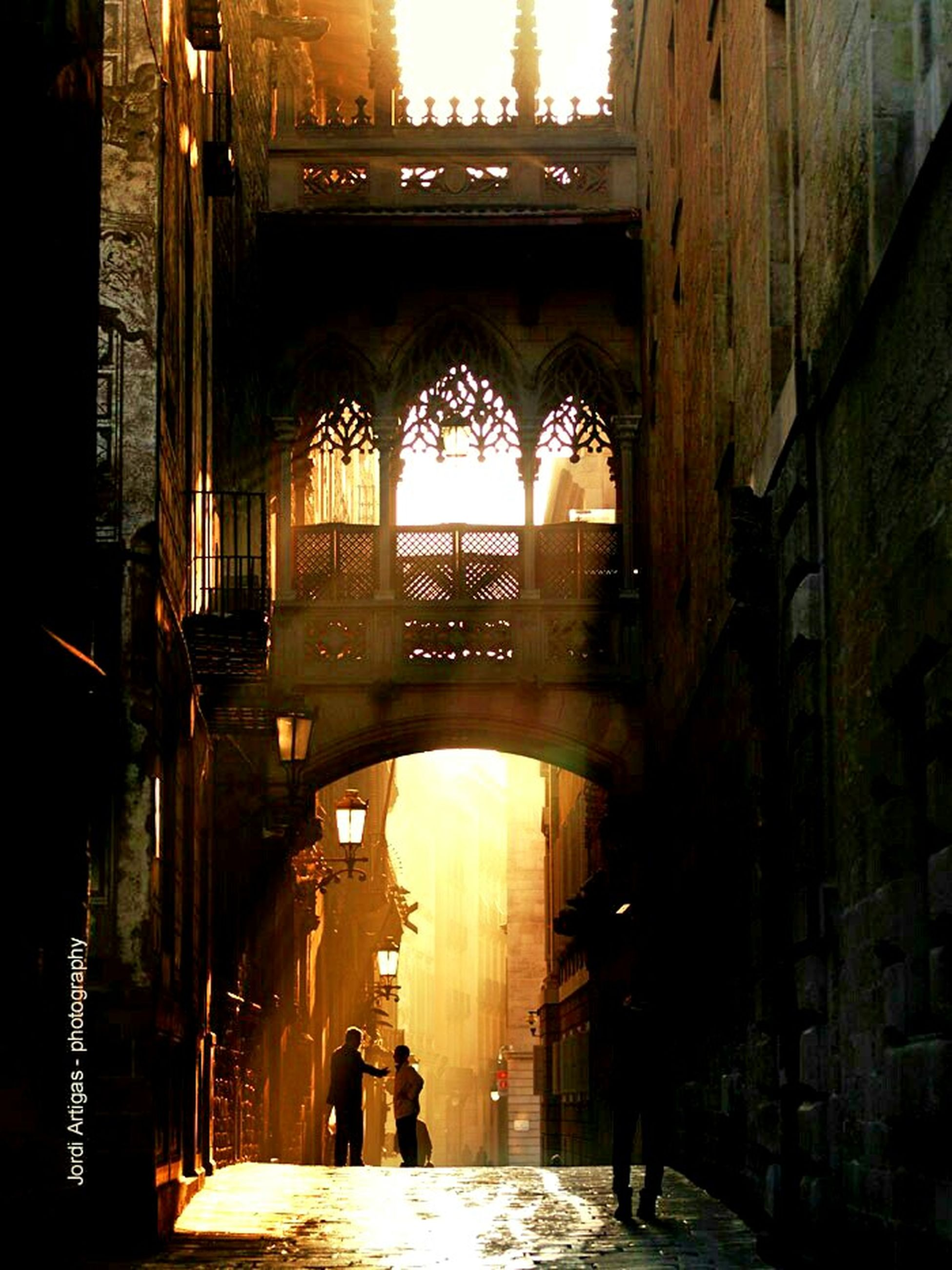architecture, built structure, arch, building exterior, bridge - man made structure, indoors, archway, connection, architectural column, history, water, men, travel destinations, incidental people, illuminated, arch bridge, walking, city, building