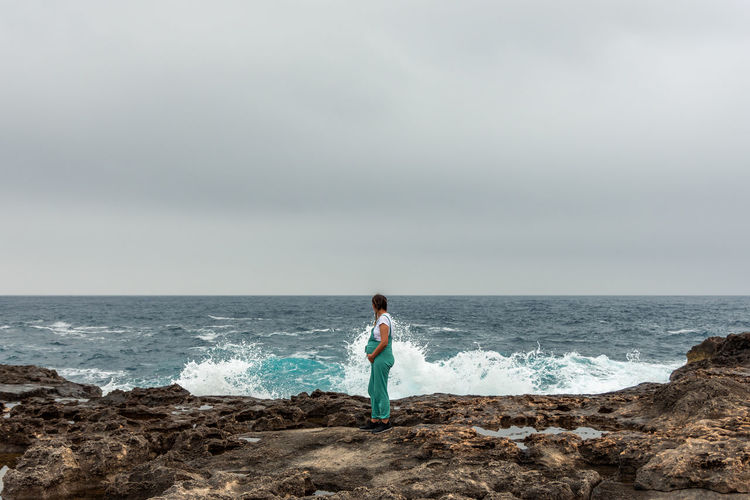 Pregnant woman dressed in green dungarees caressing her belly. waves breaking on a volcanic landscap
