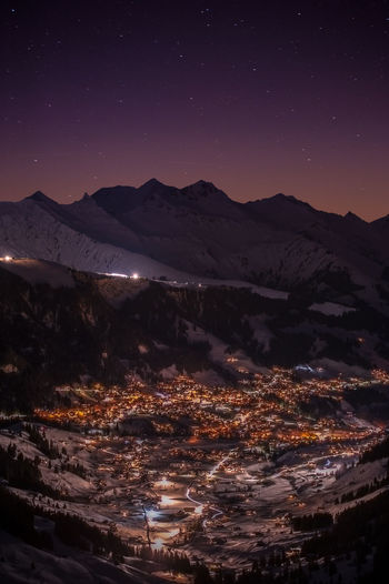 Aerial view of snowcapped mountains against sky at night