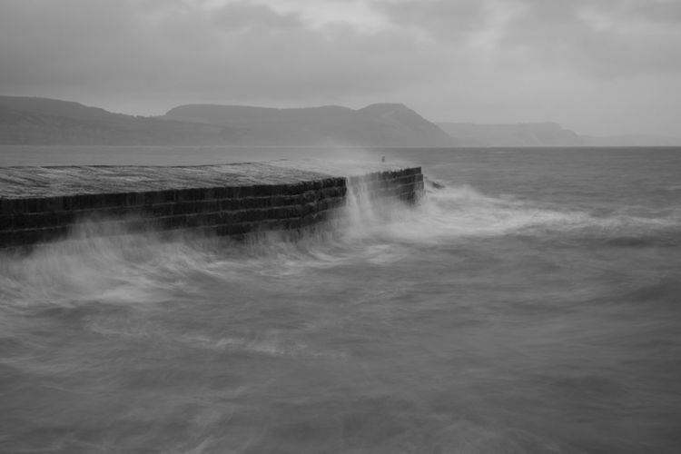 Long exposure of the waves crashing up against the pier t lyme regis in dorset in black and white