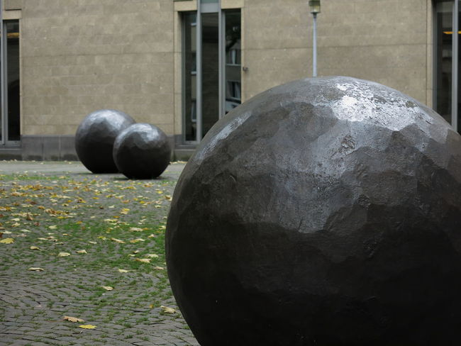 Forged spheres on a place in Cologne. Place Architecture Ball Bowl Building Exterior Built Structure Close-up Day Forged Steel Grass Hammered Metal Iron - Metal Mobility Nature No People Outdoors Sculpture Spheres Stability