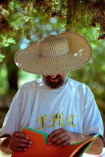47 °C / 116°F in shade. Casual Clothing Day Facial Hair Focus On Foreground Front View Hat Holding Leisure Activity Lifestyles Males  Men Obscured Face One Person Outdoors Portrait Real People Straw Hat Sunlight Tree Waist Up