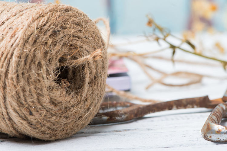 Roll of jute with dried flowers in the background and rusty scissors Gift Box Rollercoaster Rustic Background Crafting Decorated Jute Shabby Chic Vintage