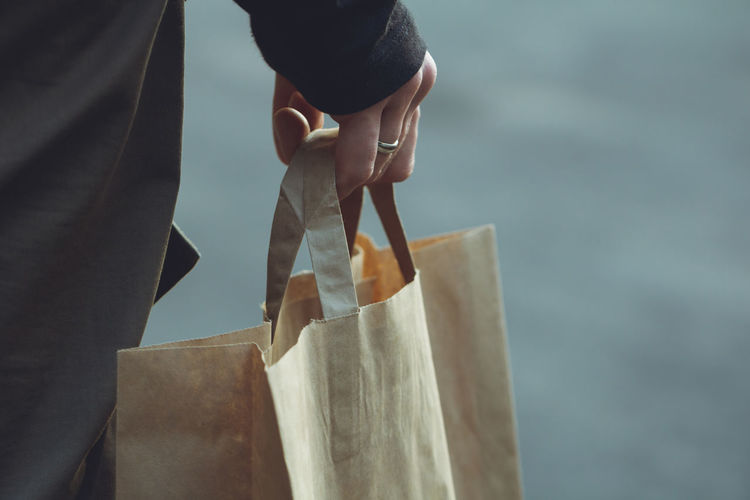 Midsection of person holding shopping bag