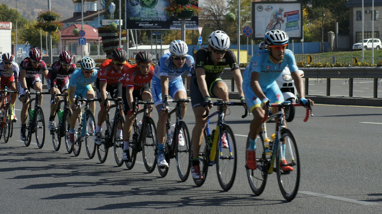 bicycle, transportation, riding, large group of people, mode of transport, street, road, cycling, men, real people, helmet, day, competition, sports race, headwear, land vehicle, racing bicycle, cycling helmet, full length, outdoors, sports clothing, sports team, people, adult, adults only