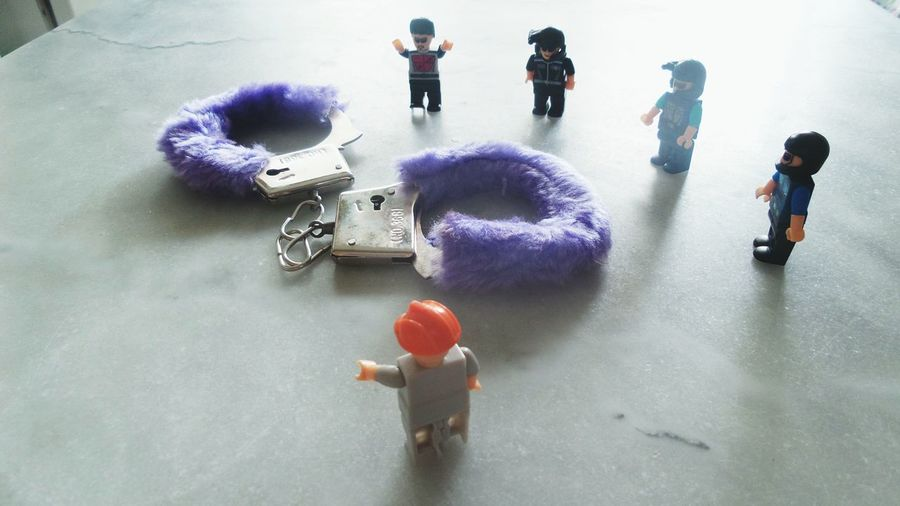 High Angle View Of Toy Police With Handcuff