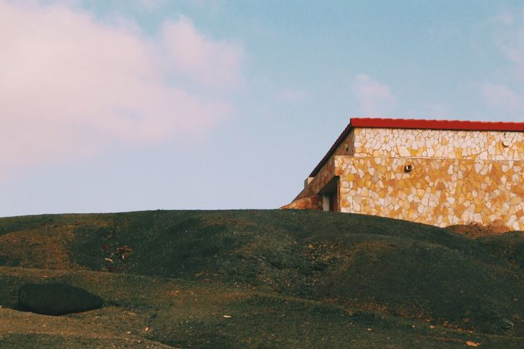 Low Angle View Of House On Hill Against Sky