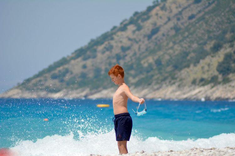 Shirtless boy standing on beach
