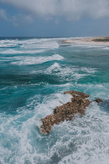 A view of the Caribbean Ocean in Aruba. Aruba Beach Photography Caribbean Sea Beach Beauty In Nature Caribbean Caribbean_beautiful_landscapes Cloud - Sky Day Horizon Over Water Island Nature No People Outdoors Rock - Object Scenics Sea Sky Water Wave
