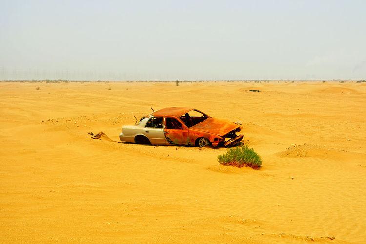 Car on desert land against clear sky