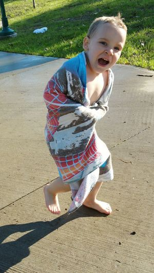 Boy Wrapped In Towel Running On Footpath