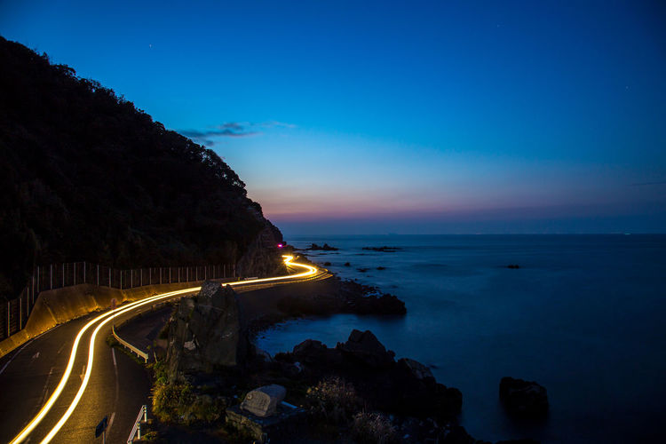 Light trail on road by sea against sky at dusk