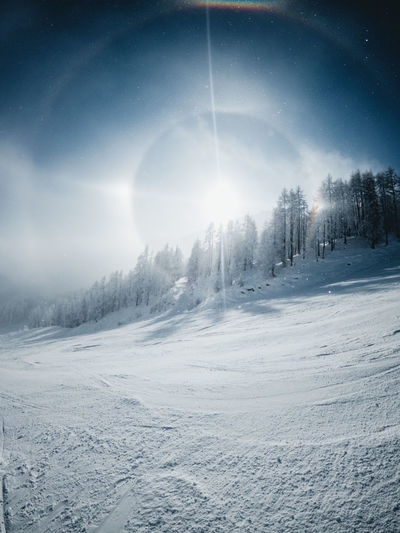 Scenic view of snow covered landscape against bright sun