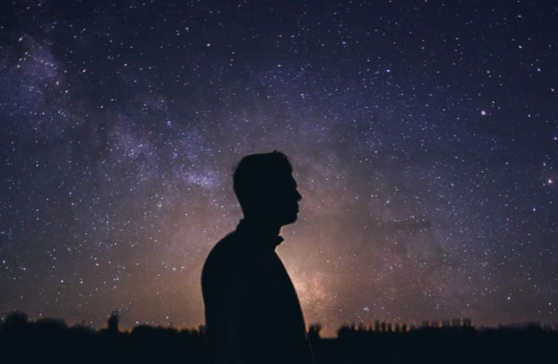Side view of silhouette man standing against star field at night