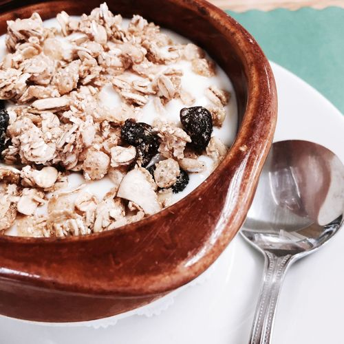 High angle view of yogurt with granola served in bowl on table
