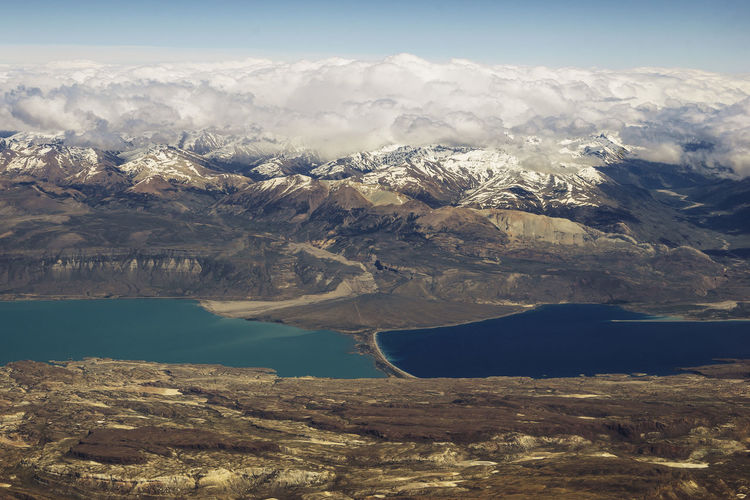Aerial view of lake and snowcapped mountains against sky