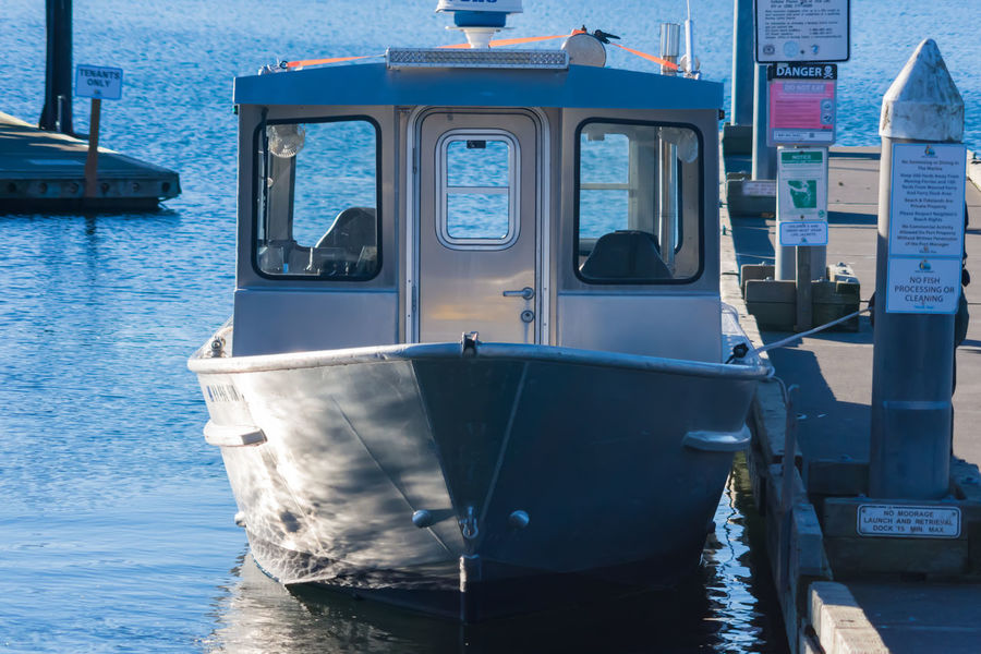 Police boat sitting at the dock Boat Boats Day Dock Door Metal Metallic Moored Nautical Vessel No People Outdoors Pacfic Northwest Police Ripples Rope Shadow And Light Shadows Shiny Signs Speed Technology Transportation Water Water Reflections Windows