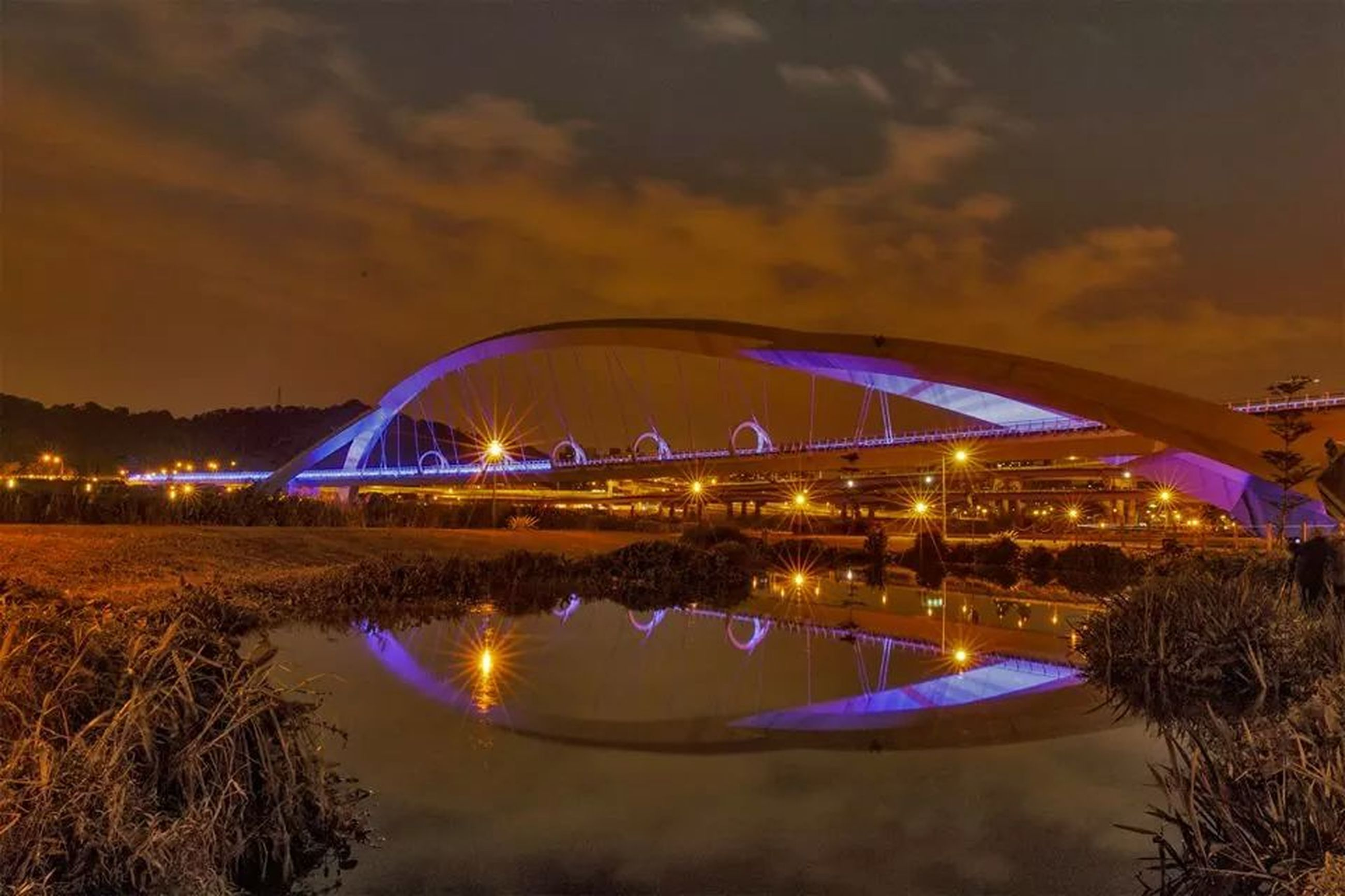 illuminated, water, sky, reflection, architecture, built structure, night, transportation, river, waterfront, ferris wheel, city, building exterior, cloud - sky, nautical vessel, long exposure, dusk, connection, outdoors, travel destinations