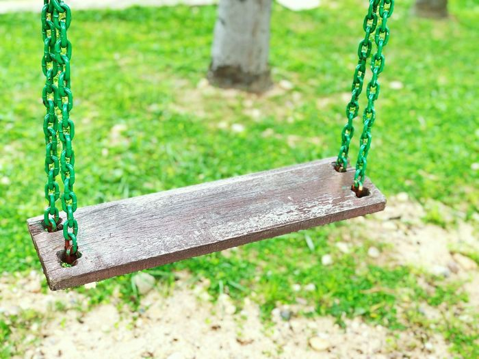Wooden swing with green metal chain isolated in green grass blurred background. Childhood Children Relaxing Liesure Wooden Swing Fun Time Playing Equipment Tool Playground Green Chain Swing Day Nature Plant Playground Focus On Foreground Grass Park Metal Hanging Park - Man Made Space Childhood Land Green Color Outdoors Outdoor Play Equipment Rope Empty