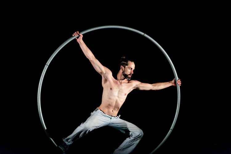 Circus Adult Agility Balance Black Background Circle Circus Geometric Shape Human Arm Indoors  Men Motion One Person Performance Plastic Hoop Shirtless Skill  Sport Strength Studio Shot Vitality Young Adult