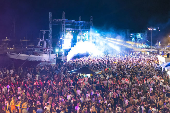 RIMINI, ITALIA - JUNE 30, 2018: Molo Street Parade Rimini, the Italian singer Fedez performs live singing his greatest hits. Artist Concert Dance Entertainment Event Fedez Rudeejay Ferris Wheel Festival Lights Live Molo Street Parade Music Musician Night Party People Performance Rimini Show Singer  Summer Deejay Crowd Tatoo