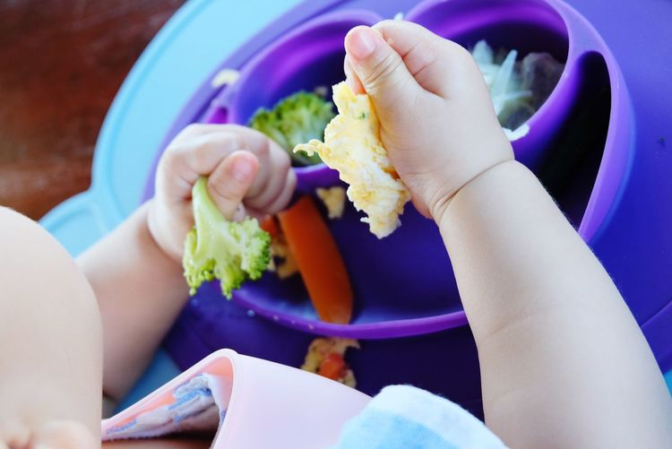 Baby eating by hand Baby Kid Baby Led Weaning Blw Human Hand Eating Women Plate Healthy Lifestyle Holding Close-up Food And Drink