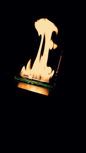 Close-up of illuminated light candle against black background