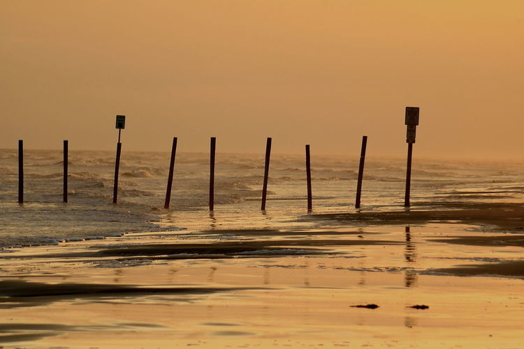 Wooden posts at shore against sky during sunset