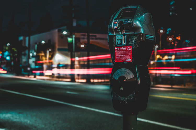Close-Up Of Telephone On Street In City At Night