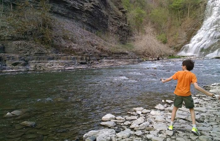 Skipping stones by a waterfall. Waterfall Waterfalls Creek Boy Skipping Rocks Skimming Stones Little Boy One Boy Boy With Glasses Finger Lakes Nature Texture Pattern Pieces Waves Daytime Summer Summertime Summer Water Wave Pattern New York Upstateny Waterscape Boy Playing Orange Color Orange