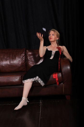 Full Length Of Woman Looking At Feather While Sitting On Sofa