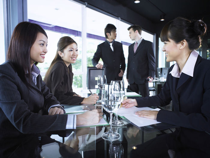 Smiling colleagues with drinks at restaurant during meeting