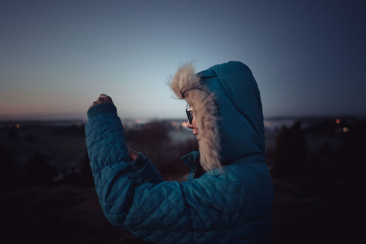 Young woman standing against sky at dusk