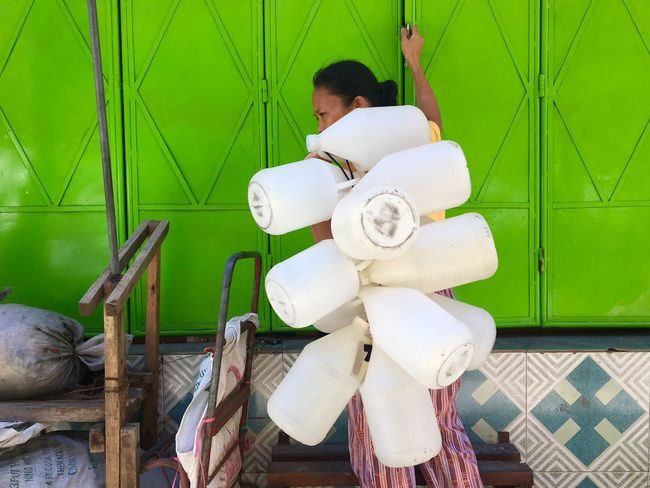 A woman carries plastic water containers at her house in Taguig, Metro Manila. Apple Green Water Container Fetching Water PLASTIC CONTAINER Woman Woman Portrait Woman Who Inspire You Plastic Philippines Manila Taguig Heroine Hardwork EyeEm Best Shots