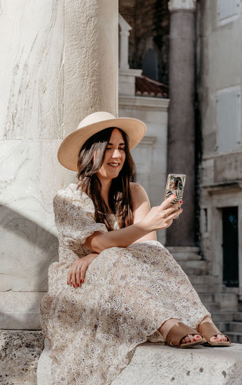Full length of young woman using mobile phone outdoors