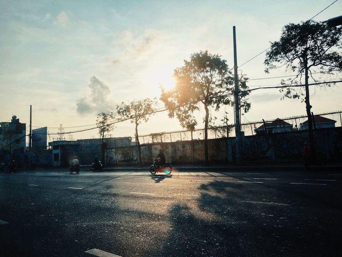 Man skateboarding on street against sky during sunset