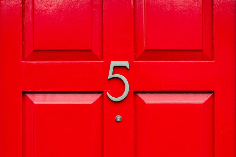 House number 5 on a red wooden front door in london