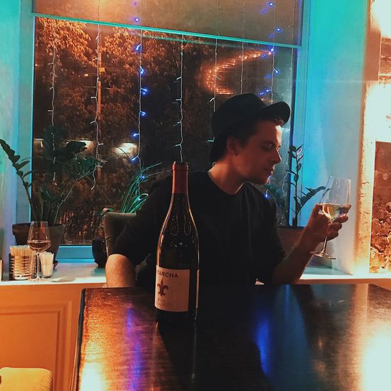 Indoors  Real People Drink Food And Drink Table One Person Refreshment Alcohol Night Leisure Activity Lifestyles Illuminated Wine Drinking Wireless Technology Home Interior Young Adult Sitting Technology Wineglass Boy Guy Gay Single Life