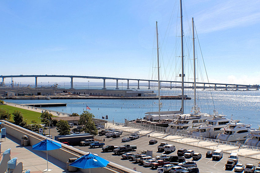 The principal architect was Robert Mosher. Construction on the San Diego–Coronado Bay Bridge started in February 1967. The bridge required 20,000 tons of steel (13,000 tons in structural steel and 7,000 in reinforcing steel) and 94,000 cubic yards of concrete. To add the concrete girders, 900,000 cubic yards of fill was dredged and the caissons for the towers were drilled and blasted 100 feet into the bed of the bay. The bridge opened to traffic on August 3, 1969, during the celebration of the 200th anniversary of the founding of San Diego. The 11,179-foot-long (3,407m or 2.1 mi) bridge ascends from Coronado at a 4.67 percent grade before curving 80 degrees toward San Diego. It is supported by 27 concrete girders, the longest ever made at the time of construction. The 30 mission-arch shaped concrete towers, designed to reflect regional historical architecture, rest on 487 prestressed reinforced concrete piles, 54 inches in diameter. Under the roadway is a steel-mesh catwalk built to facilitate bridge maintenance. Caltrans conducts routine inspections to detect concrete flaking and exposed bare metal surfaces. Painting the bridge is a never-ending job. A four-person crew works year-round to keep it protected from corrosive ocean breezes. The blue color was chosen to blend with sky and sea. Most locals refer to it as The Big Blue Bridge. In 1976 the bridge was retrofitted with special rods to protect against earthquake damage. Architecture Bridges, Highway, Freeway, Structure, Arches, Concrete, Access, Pedestrian, Vehicle, Cabrillo Bridge, Balboa Park, San Diego, California, Trees, Landscape, Tower, Railings, Scenic, Seismic, Day No People Outdoors San Diego-Coronado Bay Bridge, Arches, Pillars, Stanchions, Pilings, Girders, Steel Curved, Traffic, Sailboats, Underneath, San Diego, California,