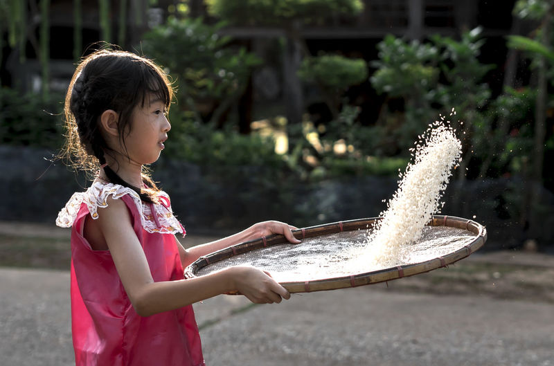 Side view of girl cleaning rice on wicker container