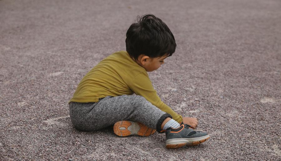 Boy playing while sitting on land