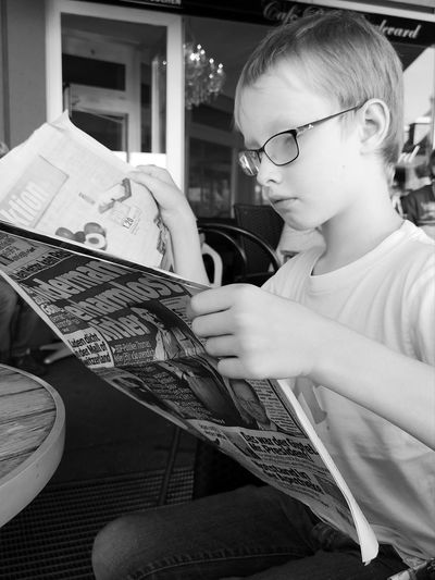 Black & White Reading Activity Blackandwhite Boy Casual Clothing Child Childhood Concentration Education Eyeglasses  Glasses Holding Innocence Leisure Activity Lifestyles Looking Men Monochrome News Newspaper Real People Sitting