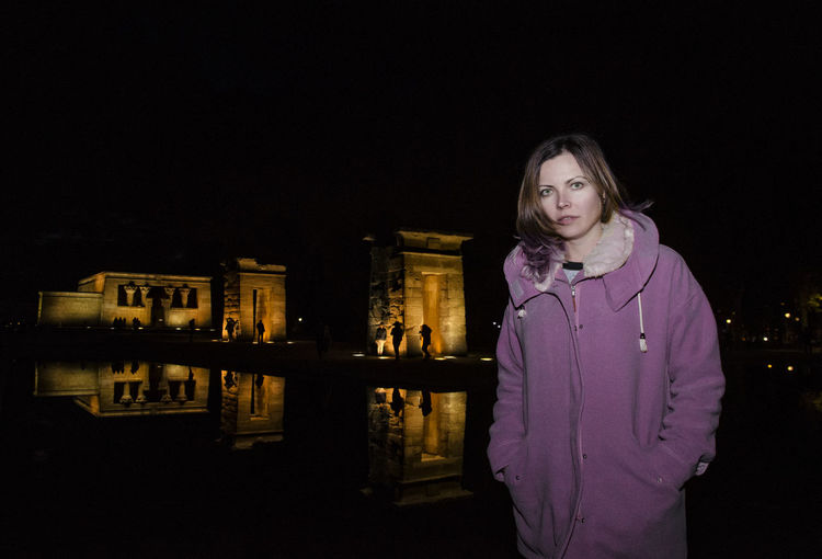 Portrait of woman standing at temple of debod during night