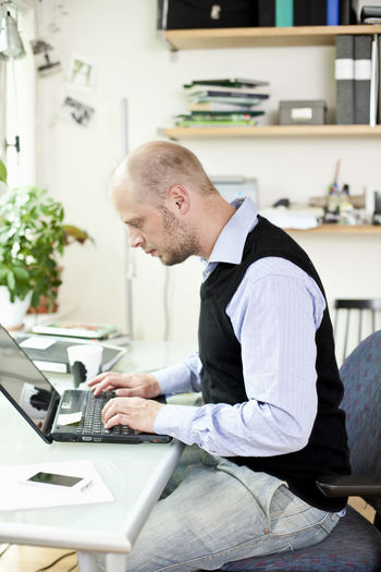 Side view of a man using laptop