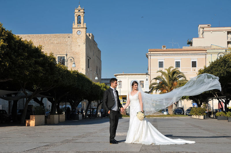 Wedding couple smiling while standing against buildings