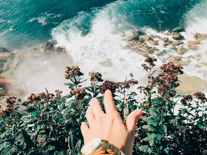 Close-up of woman hand against sea