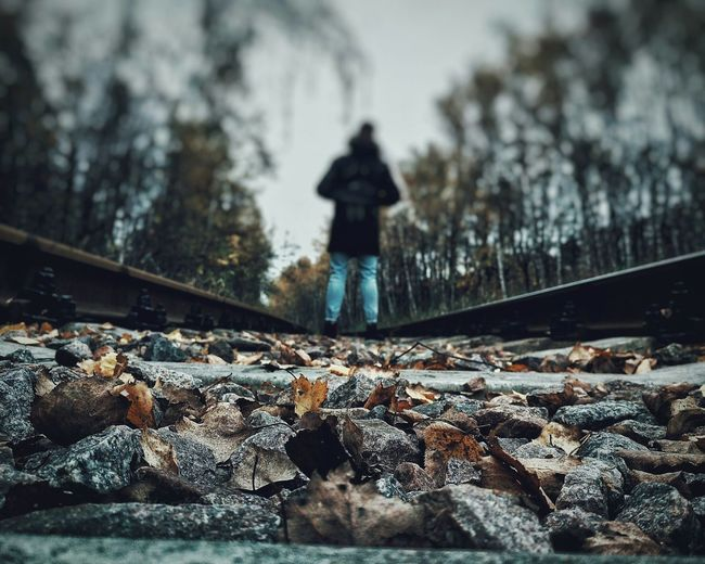 Rear View Of Person Standing On Railroad Tracks