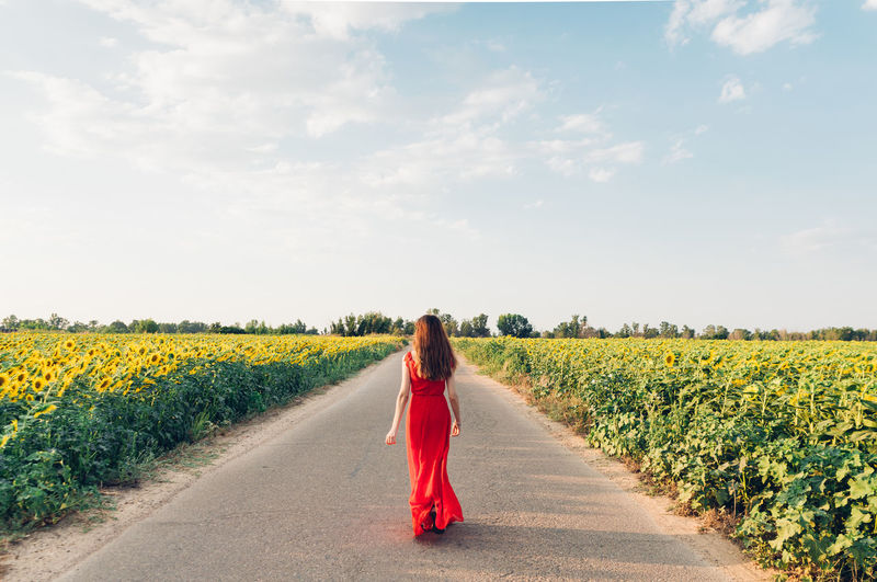 Rear view of woman on road amidst field against sky