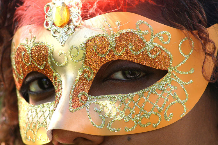 Close-up portrait of woman wearing orange carnival mask