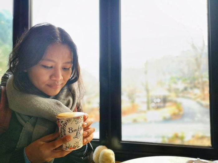 Portrait of girl drinking glass window